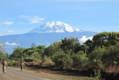 People walking along a road with Kilimanjaro in the background