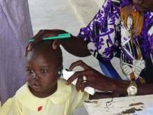 Senegalese girl having ear temperature read